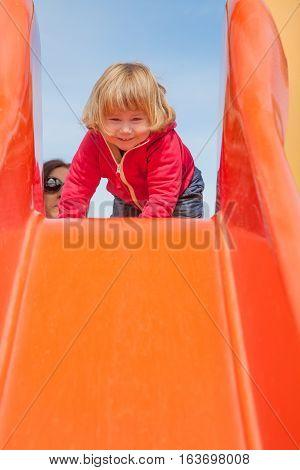 Baby Playing In Orange Slide