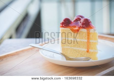 Sponge cake with cherry syrup. Peace of cherry cake served in afternoon time in cozy outdoor cafe.