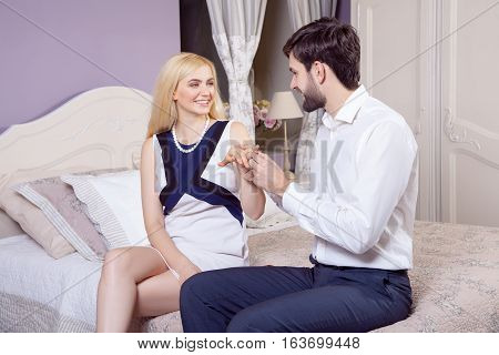 Handsome man doing a marriage proposal while offering his wife an engagement ring. Boyfriend make a marriage proposal to his girlfriend in valentine days.