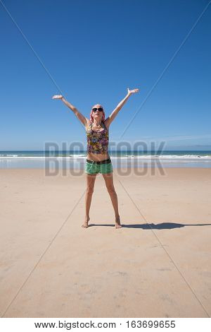 woman with headscarf green shorts opening arms at a beach