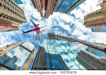 Airplane flying over modern skyscrapers on Hong Kong island. High-rise buildings in the blue dramatic sky. Concept of transport, travel and business. View from the ground level.
