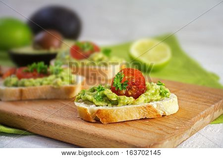 Canape sandwich with avocado cream or guacamole and tomatoes freshly prepared with ingredients on a rustic wooden kitchen board healthy party snack closeup selected focus narrow depth of field