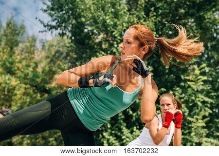 Women doing TaeBo side kicks, toned image
