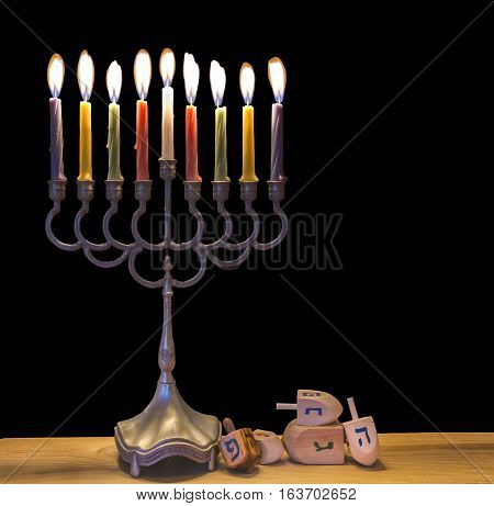 Menorah with burning candles is a major traditional Jewish symbol for Hanukkah holiday. Low key image with a black background.