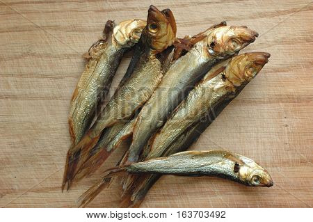 Several fishes of sprat on a wooden surface.