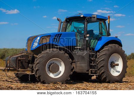Large new blue tractor plowing a field after harvest on a sunny day. The work of agricultural machinery.
