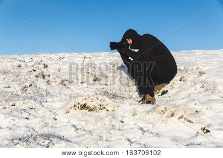 Photographer at work on the snow in winter. Adult man taking photos with his camera on a snow covered hill. Wanderlust nature and exploration concepts.