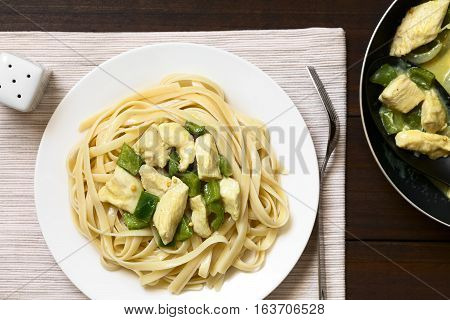 Chicken with green bell pepper and onion in mustard cream sauce on fettuccine pasta photographed overhead with natural light (Selective Focus Focus on the dish on the plate)