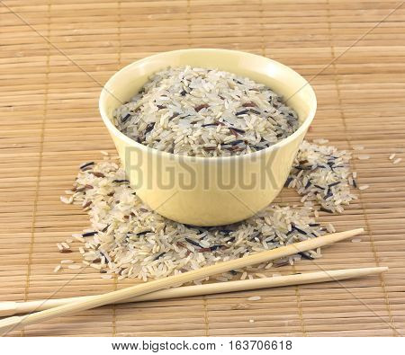China color rice and beige bowl with chopsticks on brown straw mat closeup
