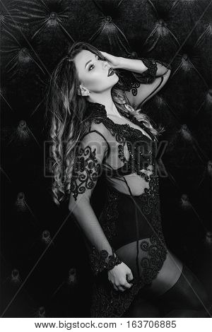 Young beautiful attractive and hot long hair woman in black underwear near black velvet wall in photo studio monochrome