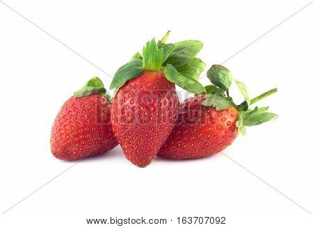 Three ripe appetizing red strawberry fruits with green leaves isolated on white closeup