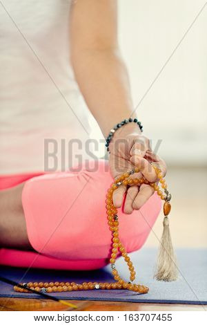 Young woman meditating with rosary beads, toned image