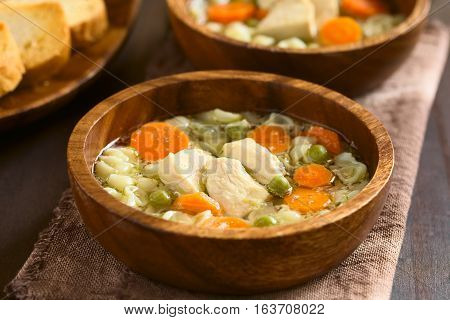 Homemade chicken soup with pea carrot and small shell pasta in wooden bowls photographed with natural light (Selective Focus Focus on the front of the chicken in the first soup)