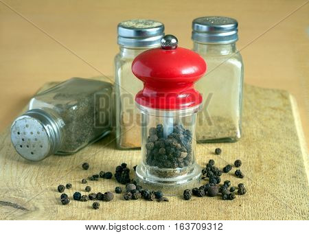 Still life with black peppercorn, hand mills and glass spice jars on kitchen table. Photo closeup