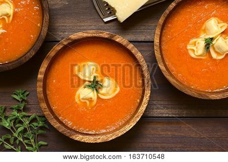 Homemade fresh cream of tomato soup with tortellini garnished with fresh oregano served in wooden bowls photographed overhead on dark wood with natural light