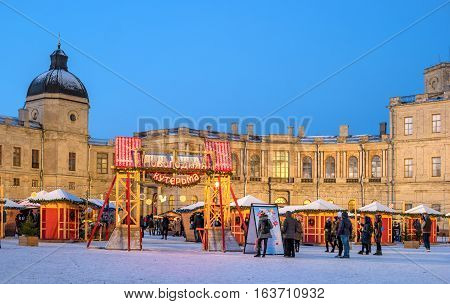 Gatchina, Russia - January 2, 2017: Gatchina Palace, New Year's Fair on the parade ground. Fair. Above the gate inscription - Christmas mess. People buy souvenirs and sweets. Photo taken in the evening.