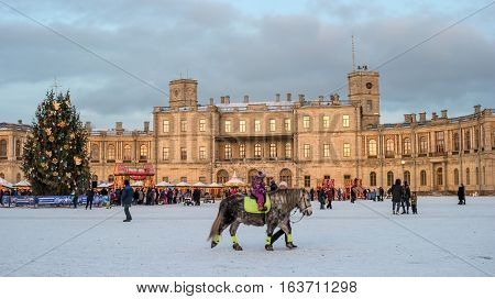 Gatchina, Russia - January 2, 2017: Gatchina Palace, New Year's Fair on the parade ground. People walk around the fair. Children ride on a horse. Photo taken in the evening.