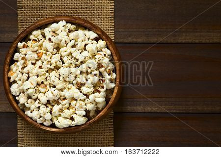 Homemade fresh savory popcorn with cheese garlic and dried oregano in wooden bowl photographed overhead on dark wood with natural light (Selective Focus Focus on the top of the popcorn)
