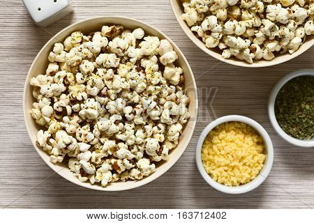 Homemade fresh savory popcorn with cheese garlic and dried oregano in bowls photographed overhead with natural light (Selective Focus Focus on the top of the popcorn)