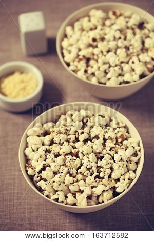 Homemade fresh savory popcorn with cheese garlic and dried oregano in bowls photographed with natural light (Selective Focus Focus in the middle of the first bowl) (Digitally Altered: Toned Image)
