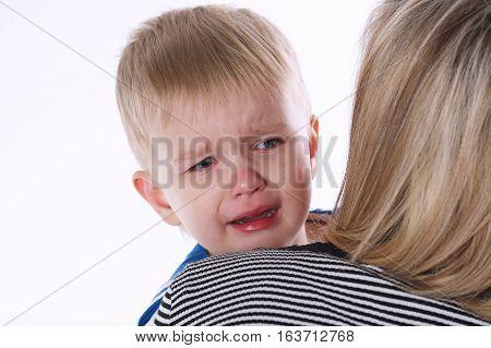 photo of little crying boy on moms shoulder