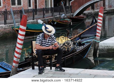 Venice, Italy - July 28th, 2011: Portrait of a young gondolier using a mobile phone while waiting for clients near a Venetian canal.Gondola is a major mode of touristic transport in Venice and one of the most specific icon of the city.