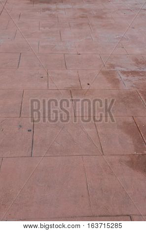 Stamped concrete floor outdoor pavement worn out, perspective, appearance of natural stone, mimics colors and textures of material pavers, red square pattern