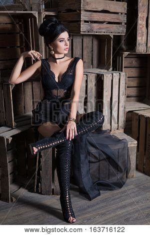 Luxury beautiful pin-up sexy woman in black dress in dark vintage interior