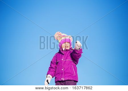 A four year old girl upper body wearing purple winter coat mitts and snow hat squinting into the distance pointing with one hand