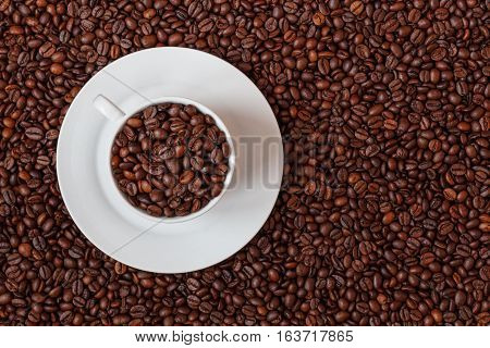 White coffee cup filled with coffe beans