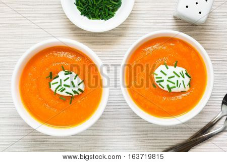 Fresh homemade cream of carrot soup with dollop of cream or yogurt and chives on top served in bowls photographed overhead with natural light (Selective Focus Focus on the soups)