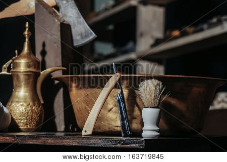 Vintage barber or shaver tools on wooden table. Old razor with cutthroat blade copper basin water jug axe and shaving brush in barbershop or hairdressing saloon