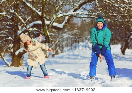 Children play in snowy forest. Toddler kids outdoors in winter. Friends playing in snow. Christmas vacation for family with young children.