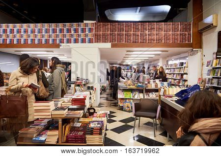 ATHENS GREECE - MAR 26 2016: Large group of people reading books before buying them in Athens bookstore during night sales