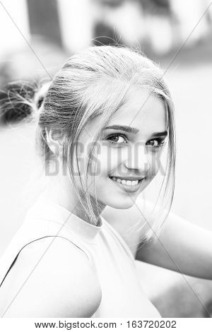 Pretty young woman or girl with tied in bun blonde hair in shirt with cute smiling face on blurred background black and white