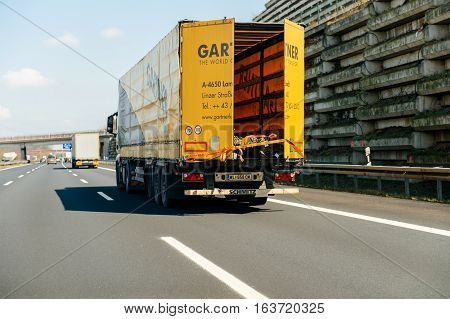 GERMANY - MAR 26 2016: POV point of view of a driver looking at Mercedes-Benz cargo truck with Gartner Speditions logotype transporting steel tubes driving on bundesautobahn or Federal Motorway highway street signs to Mannheim Karlsruhe Rastatt-Nord Baden