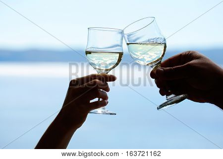 Hands of male and female clinck wineglasses of white wine on blurred seascape background.
