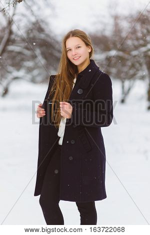 season christmas or holidays and people concept - smiling young girl in winter clothes outdoor.