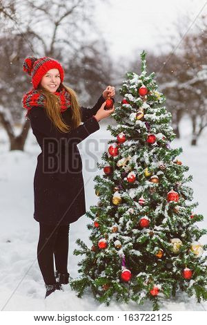 Cute teenager or girl decorating christmas tree outdoor.