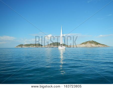 Sailboat at anchor in the ocean with mail sail hoisted and islands in the background.