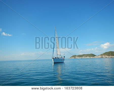 Sailboat at anchor with main sail hoisted.