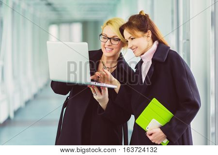 Two smiling Attractive businesswoman using laptop at office lobby.
