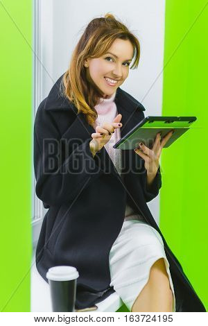 fashion business woman dressed in coat holding tablet sitting on window sill.
