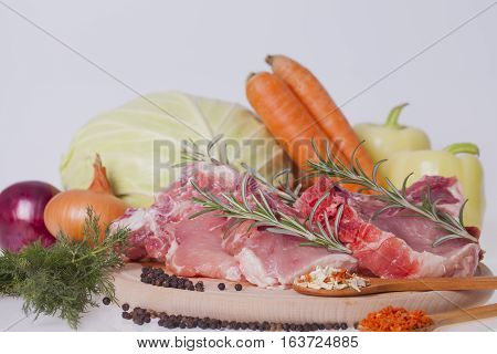 fresh pork meat with vegetables on wooden board