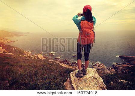 successful hiker use cellphone taking photo on seaside mountain peak rock
