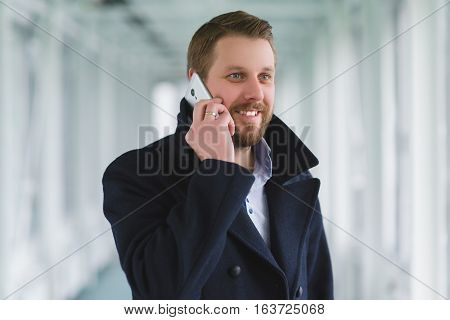 young businessman with cell phone dressed coat