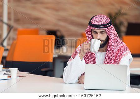 Arabian businessman working in modern startup office.