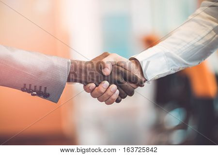 Handshake between african and a caucasian man.