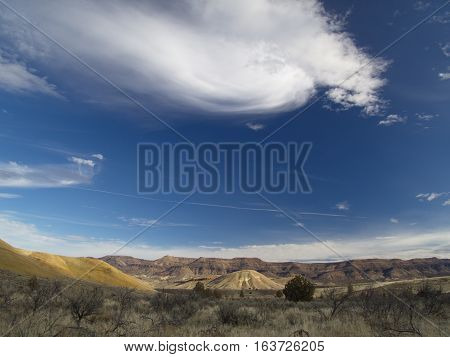 A cloud swirls over the bright Painted Hills in the John Day Fossil Beds in Eastern Oregon on a sunny winter day.