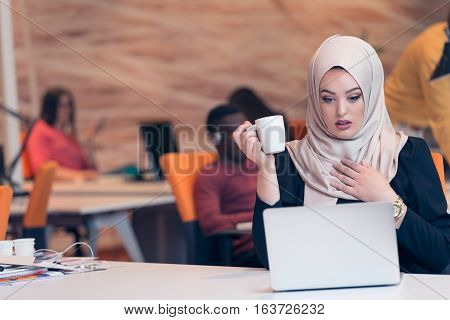 Young Arabic business woman wearing hijab, working in her startup office. Diversity, multiracial concept